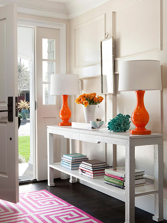 Neutral walls and furnishings but still so much COLOR in this entryway. Those orange lamps are awesome!   100+ Beautiful Mudrooms and Entryways at Remodelaholic.com
