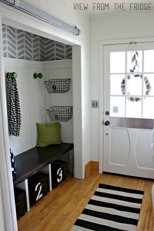 I really like the mix of patterns in this black and white entry. Perfect storage bench with rolling bins!