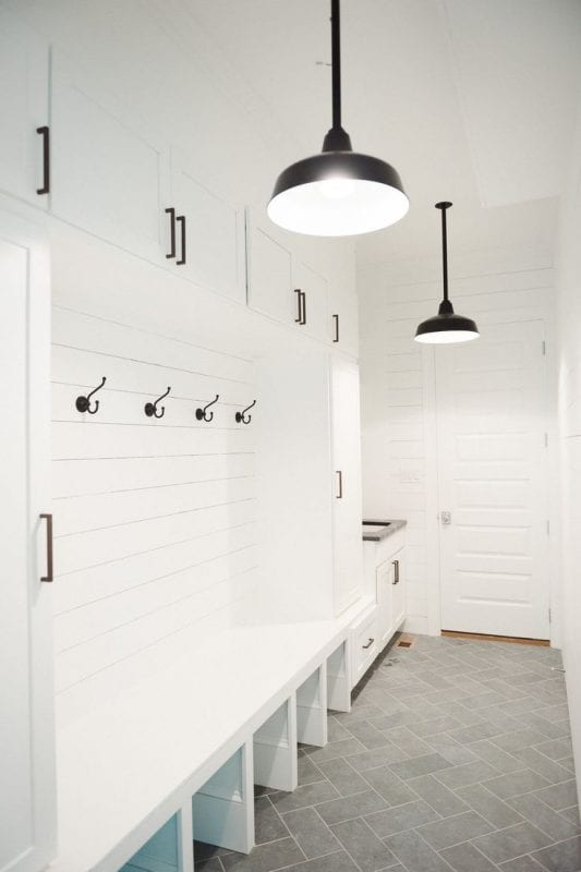 This black and white mudroom is beautiful! Love the gray tile floor.