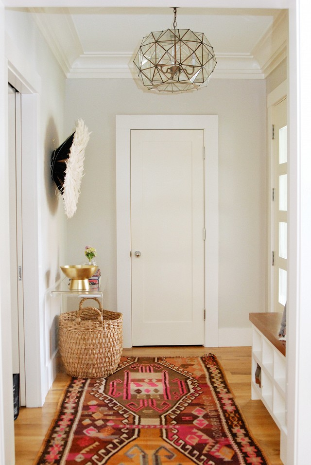 That rug is amazing, and I love the light in this entry hall! I need a shoe cubby bench, too.   100+ Beautiful Mudrooms and Entryways at Remodelaholic.com