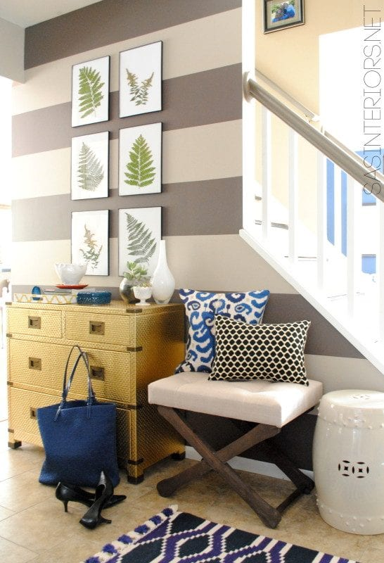 Gold and navy entryway, love the bench and plant prints | 100+ Beautiful Mudrooms and Entryways at Remodelaholic.com