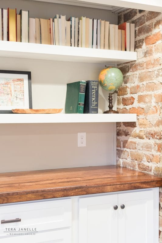 A beautiful travel-inspired master bedroom with an exposed brick wall and a beautiful built-in bookshelf and storage nook. Tera Janelle on Remodelaholic.com