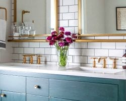 feat bathroom remodel with gold mirrors and faucets, schoolhouse lighting, dark vanity, subway tile Hammer and Hand