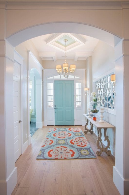 Turquoise and orange accents in the entryway, plus the mirror and table are AMAZING   100+ Beautiful Mudrooms and Entryways at Remodelaholic.com