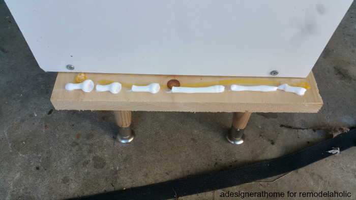 squeeze a small layer of construction adhesive onto the board and place the unit atop the board, clamp into place