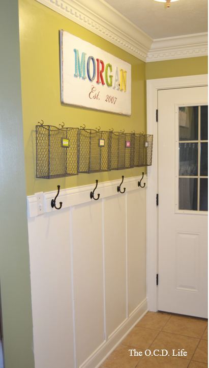 Awesome entryway command center with wire baskets and hooks above the board and batten   100+ Beautiful Mudrooms and Entryways at Remodelaholic.com