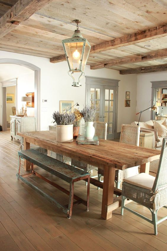 Fancy farmhouse dining room with rustic table and bench and open beams via