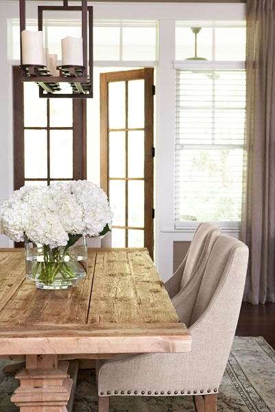 Cute farmhouse dining room with swoop arm chairs and rustic wood table by Linda McDonald Design