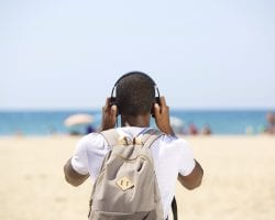 Young man with headphones and bag standing at the beach from behind