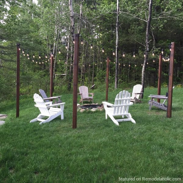 DIY easy outdoor string lighting posts around a fire pit and seating area, featured on @Remodelaholic wm