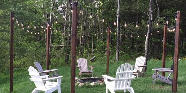 fb DIY easy outdoor string lighting posts around a fire pit and seating area, featured on @Remodelaholic