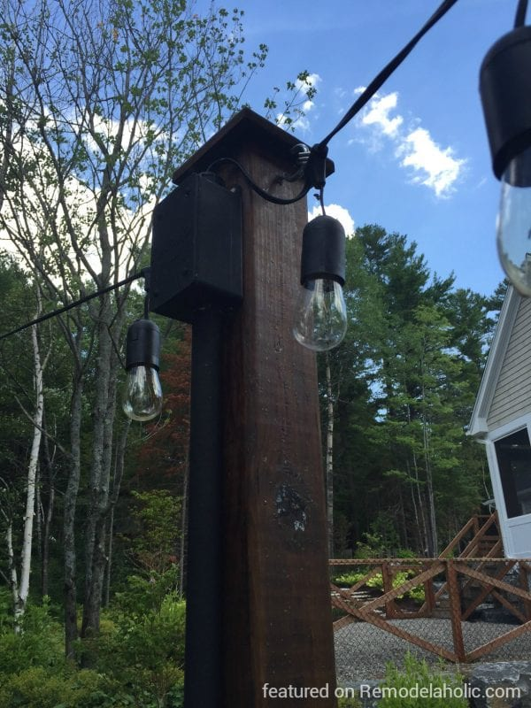 how to hang string lights on posts around a fire pit, featured on @Remodelaholic wm