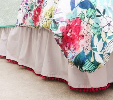 Embellished bed skirts are expensive! If you are on a budget, create this semi-homemade pom pom bedskirt without breaking the bank. It's a high-end look on a budget!
