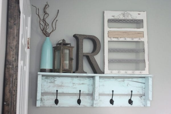 Pallet coat rack with hooks and 16 clever organization pallet hacks featured on remodelaholic.com
