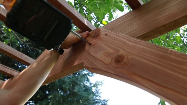 attaching a curved cross-piece to the backyard wedding garden arbor