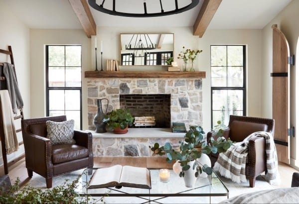Farmhouse Living Room: Fixer Upper La Pequeña Colina with stone fireplace and wood beams
