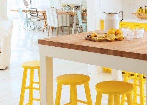 Neutral white with sunny yellow kitchen accents, cabinets, bar stools via Style Carrot | How to add Yellow in Kitchen decorating #Remodelaholic