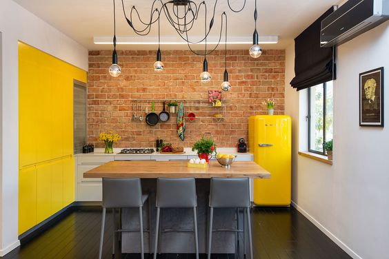Sunny yellow kitchen accent wall and fridge with exposed brick wall, modern kitchen | Yellow Kitchen Inspiration #Remodelaholic