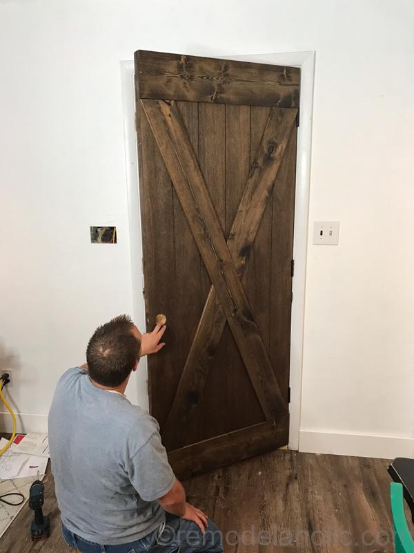 DIY Wood Barn Door on Hinges for $25 #remodelaholic