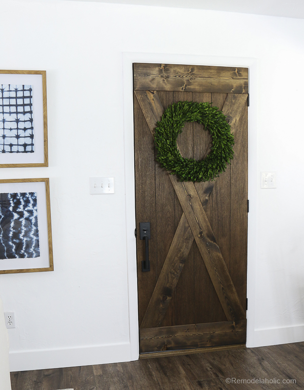 Make that dated wood door shine like new again with a farmhouse style barn door look! Plus, this door update is designed to use the existing hinges and door framing, no custom work required. #remodelaholic