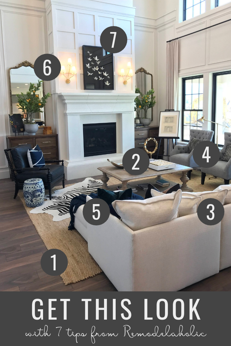 How to decorate a modern farmhouse living room with a neutral sofa and armchairs plus a beautiful paneled fireplace | Tips to get this look at Remodelaholic | Home designed by Arive Homes, Utah Valley Parade of Homes 2018 #getthislook #modernfarmhouse #remodelaholic #uvph