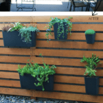 How to cover up a cinder block fence with a wood slat garden wall with vertical hanging planters, The Garden Glove featured on Remodelaholic.com