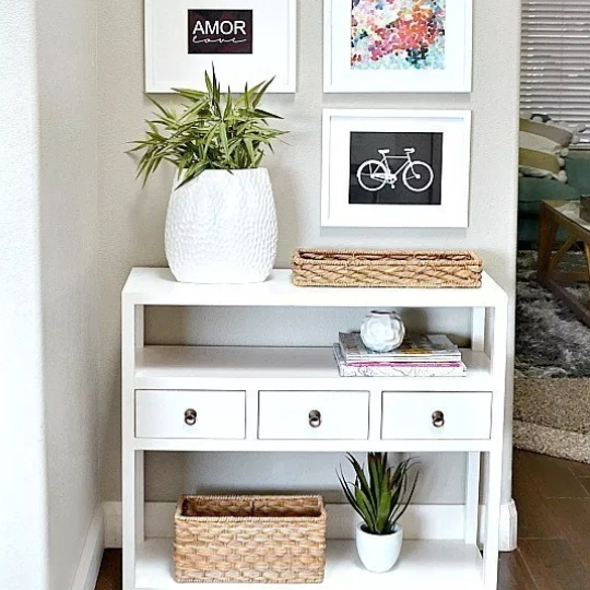 White Dresser With Three Small Drawers And Three Shelves With Wicker Baskets And Greenery
