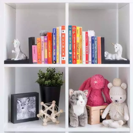 White Square Bookshelves With Colorful Children's Books And Unicorn Book Ends And Stuffed Animals, Cat Photo In Picture Frame, Plant And Wooden Star Toy