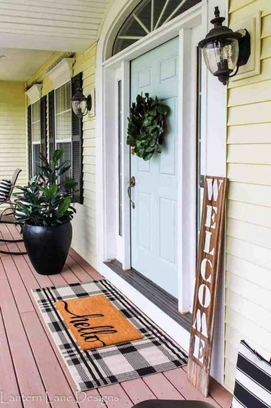 Gorgeous Yellow Home With Robin Egg Blue Door And Black And White Plaid Door Rug With Hello Rug On Top And Black Pot With Greenery And Wooden Chairs And Welcome Sign