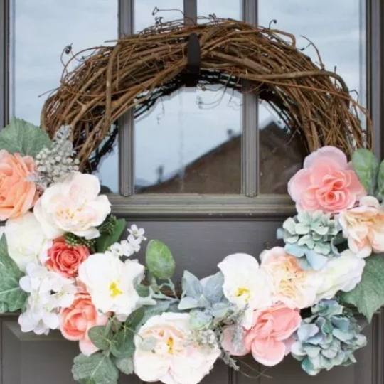 Grey Front Door With Twig Wrath And Pretty Pink And White And Blue Flowers With Green Leaves Throughout