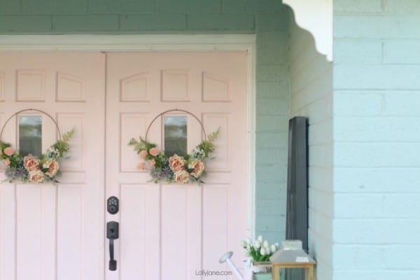 White Double Doors With Beautiful Pink Floral Wreaths On A Light Blue House