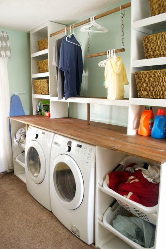 White Front Load Washer And Dryer With Stained Wood And Painted White Shelving And Clothes Rod