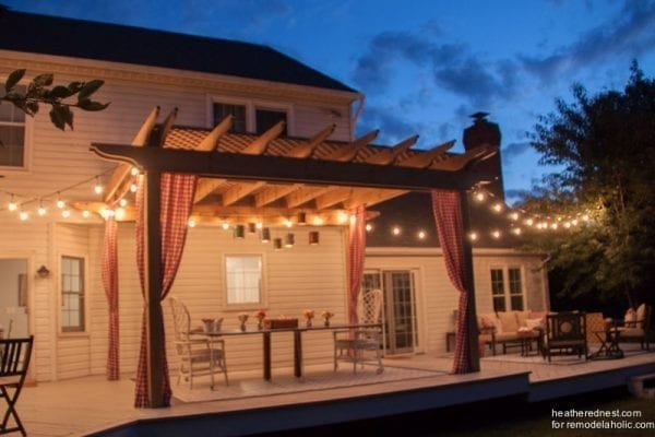 Pergola With Hanging String Lights Curtains And Dinner Table Shown At Night