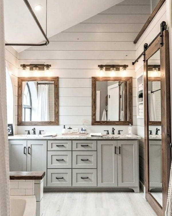 Shiplap Wall Of Bathroom With Colored Cabinets And Raw Wood Mirrors