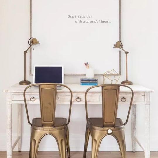 Chic Neutral Homework Station With White Table, Gold Chairs And A Large White Print With Small Text