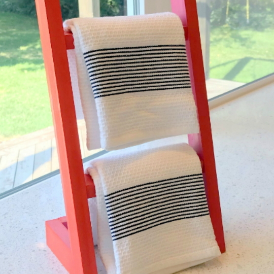 Coral Painted Wood Towel Ladder Holding Two White Kitchen Towels In Front Of Window Overlooking Grass