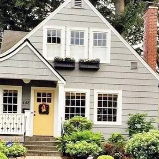 Green Home With White Trimmed Windows With Window Flower Boxes And A Yellow Front Door