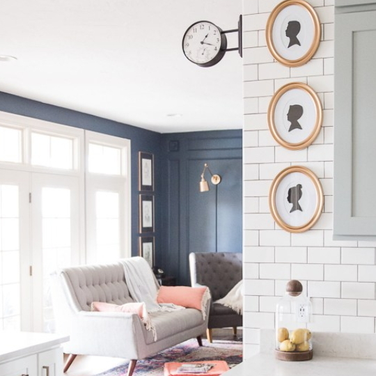 Open Living Room With White Trimmed Windows And Blue Walls With Greay Couch And Coral Blanket, White Brick Wall Showing In The Corner With Oval Silhouette Profiles