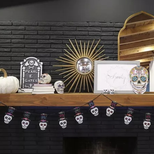 Black Brick Fireplace With Light Brown Stained Shelf With Skull Decor And Garland