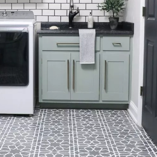 Grey Patterned Tile Floor With Mint Green Cabinets, Black Countertop And White Brick Wall