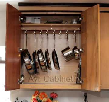 Open Stained Wooden Cupboard With Hanging Stainless Still Pots And Pans