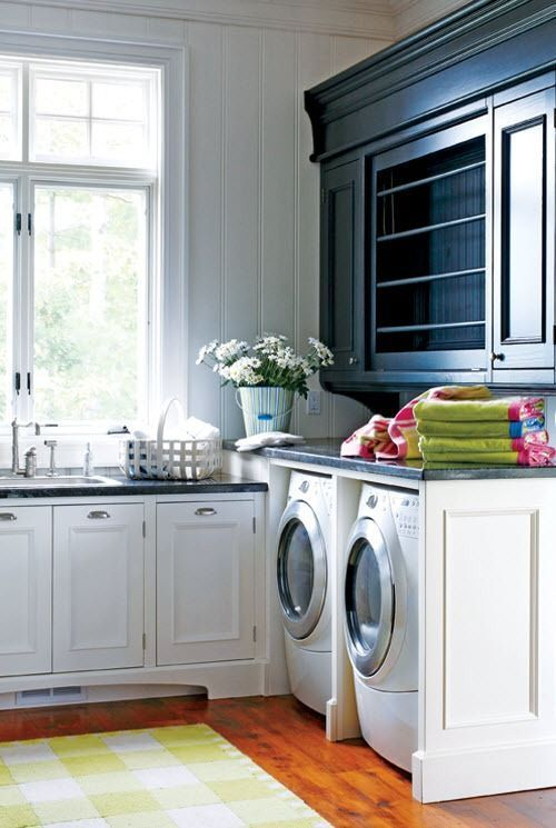 Stained Wood Floor, White Cabinets And Black Countertops Over White Washer And Dryer And Hanging Cupboard