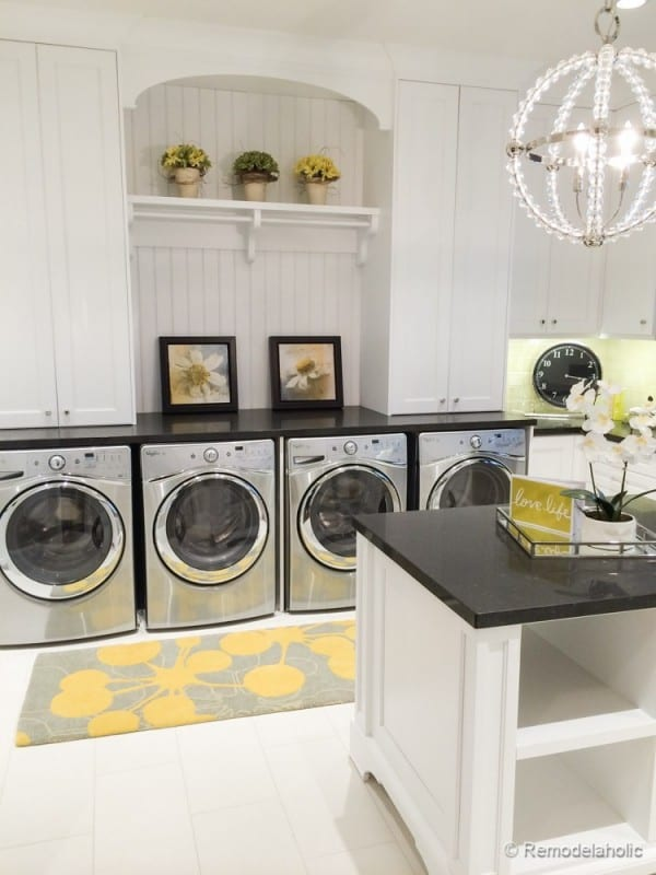 White Tile Floor With White Shiplap Walls And White Cabinets And Back Counters On Top Of Stainless Steel Front Load Washers And Dryers, Four Machines