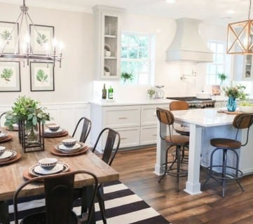 Stained Wood Floor With Black And White Striped Rug Under Wooden Table And White Walls And Cabinets And Counters