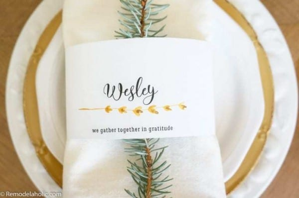 Tablescape With White And Gold Accents, White Napkin, Pine Branch, And Printed Name Card