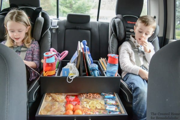 Two Kids In Car Seats With Books, Sippy Cups, And Snacks In An Organizer Between Them