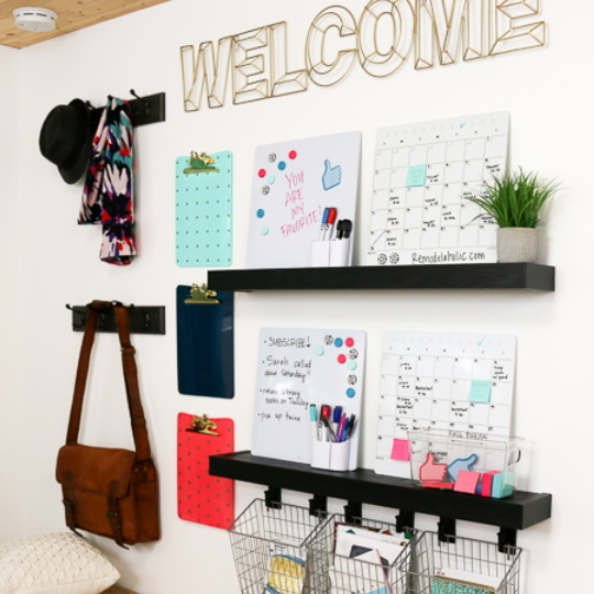 White Wall With Black FLoating Shelves And Hanging Baskets And Calendars And Clipboards And Hooks