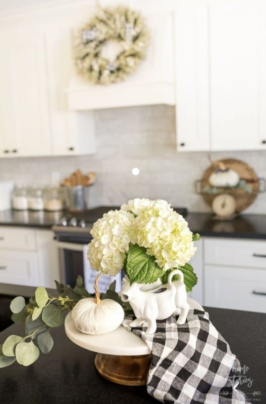 White Cupboards, Off White Backsplash, Black Countertops, White Flowers With Green Leaves