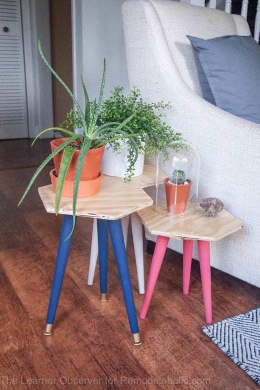 Three Hexagon Shaped Tables Of Varying Heights With Blue Legs, Pink Legs And White Legs