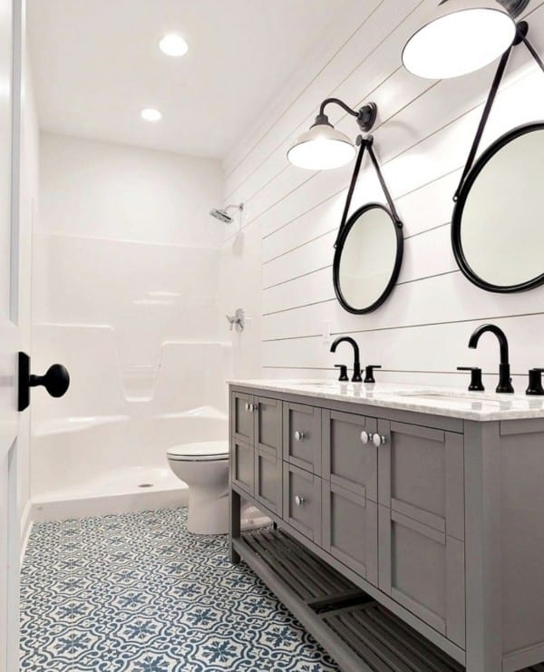 Bathroom With Horizontal Shiplap Walls And Hanging Circle Mirrors, Double Sinks, Blue And White Patterned Tile Floor